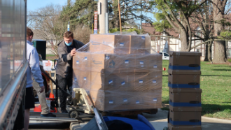 loading pallet of boxes onto truck outside the library